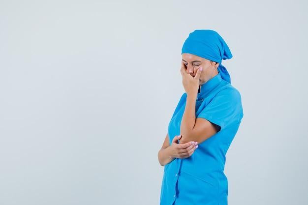 Médica, mantendo a mão no rosto em uniforme azul e olhando melancólica, vista frontal.