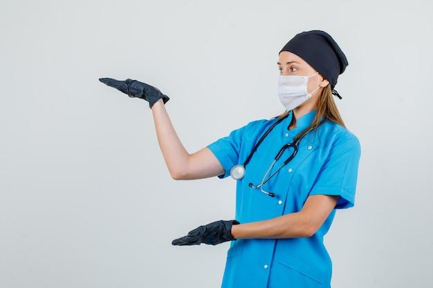 Médica mantendo as palmas das mãos abertas para mostrar algo no uniforme, luvas, vista frontal da máscara.
