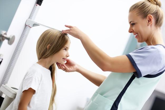 Médica medindo altura de menina na clínica