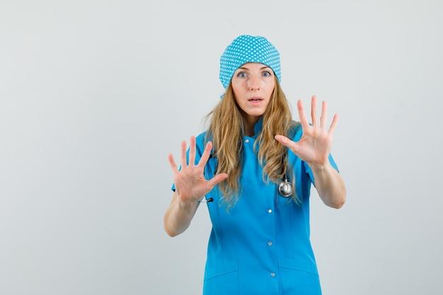 Médica mostrando as palmas das mãos de forma preventiva em uniforme azul e parecendo assustada.
