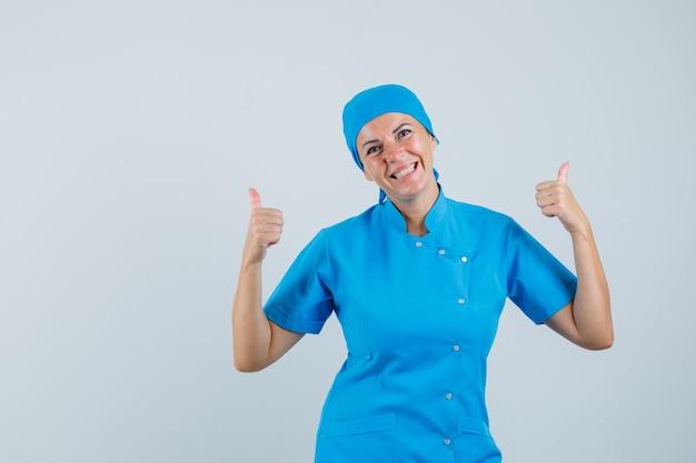 Médica mostrando dois polegares para cima em uniforme azul e olhando alegre, vista frontal.