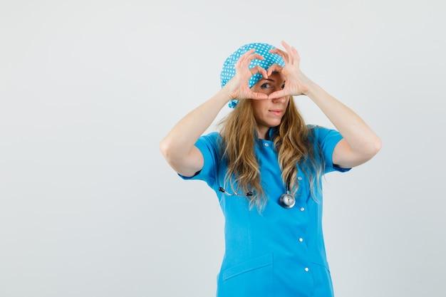 Médica mostrando gesto de coração em uniforme azul e parecendo alegre