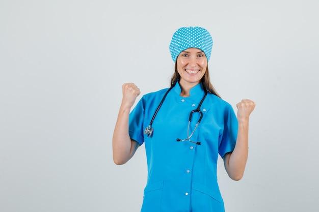 Médica mostrando gesto de vencedor em uniforme azul e parecendo alegre
