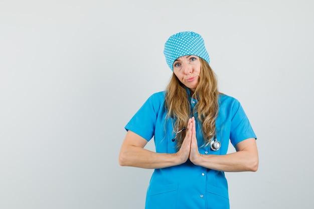 Médica mostrando gesto namastê em uniforme azul e parecendo indefesa.