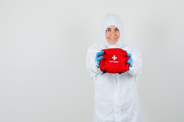 Médica mostrando kit de primeiros socorros em traje de proteção, luvas e parecendo otimista