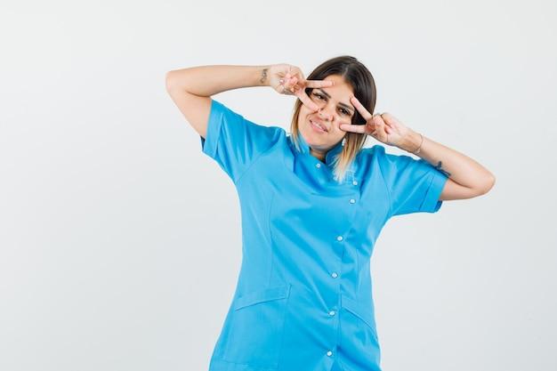 Médica mostrando o sinal v perto dos olhos, com uniforme azul e parecendo confiante