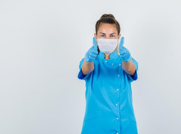 Médica mostrando os polegares em uniforme azul