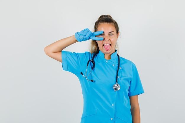 Médica mostrando sinal-v no olho de uniforme azul
