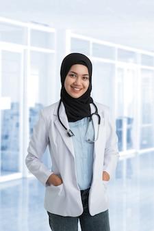 Médica muçulmana atraente com jaleco branco sorrindo