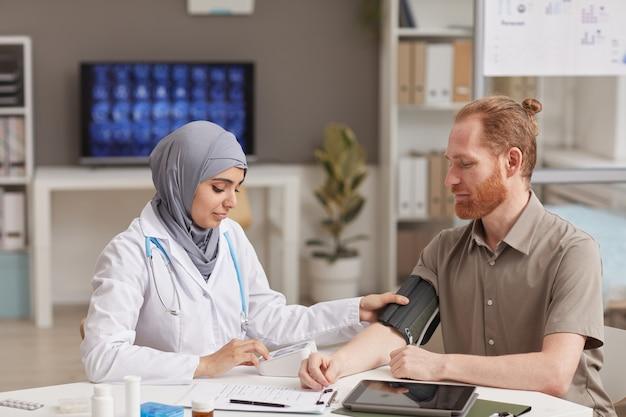 Médica muçulmana medindo a pressão de um paciente do sexo masculino durante sua visita ao hospital