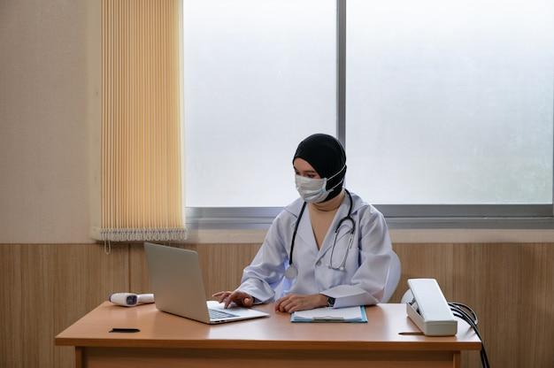Médica muçulmana usando hijab em uniforme médico usando laptop e esfigmomanômetro, termômetro infravermelho na mesa do hospital
