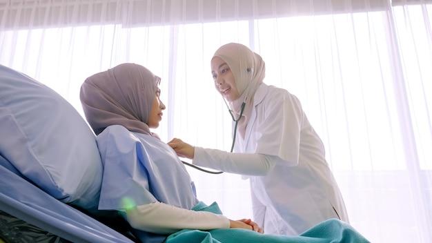 Médica muçulmana, verificando a saúde do paciente no quarto do hospital.