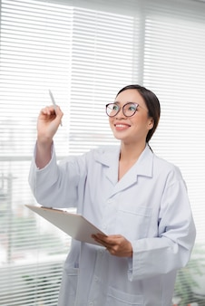 Médica mulher asiática escrevendo algo com marcador
