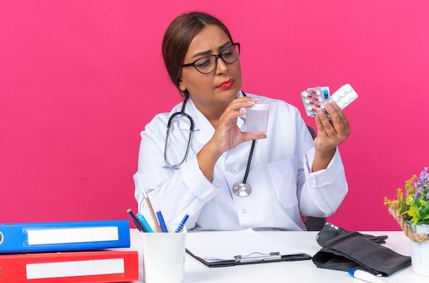 Médica mulher de jaleco branco com estetoscópio furando diferentes pílulas e o frasco de teste olhando para eles com uma cara séria sentada à mesa sobre a parede rosa