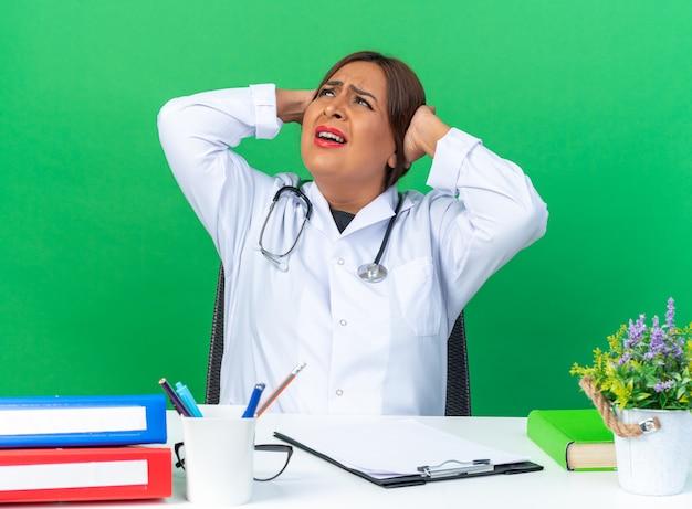 Médica mulher de jaleco branco com estetoscópio, olhando para cima confusa e descontente, sentada à mesa no gramado
