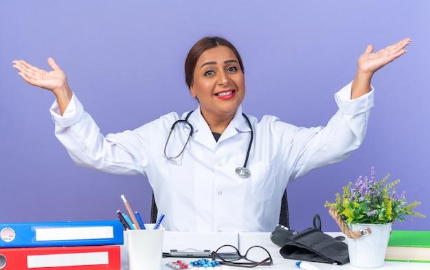 Médica mulher de jaleco branco com estetoscópio olhando para frente feliz e positiva, sorrindo alegremente, espalhando os braços para os lados, sentada à mesa sobre a parede azul