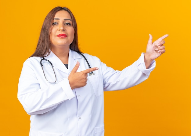 Médica mulher de meia-idade com jaleco branco com estetoscópio e sorriso confiante apontando com o dedo indicador para o lado