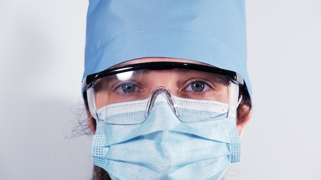 Médica na máscara médica descartável, óculos de proteção de plástico e tampa de têxteis, retrato de um médico cansado com olhos tristes, close-up