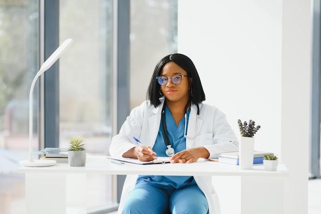 Médica negra bem-sucedida sorrindo no escritório