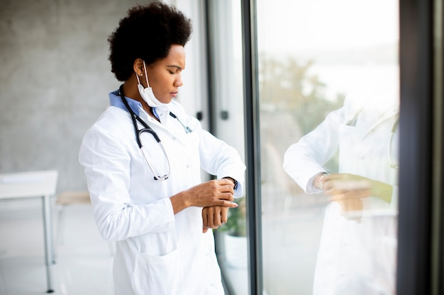 Médica negra parada junto à janela do consultório médico verificando as horas de serviço