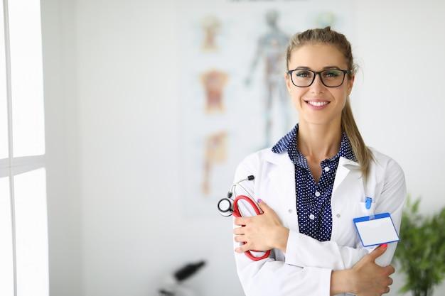 Médica no consultório médico está segurando um estetoscópio e sorrindo