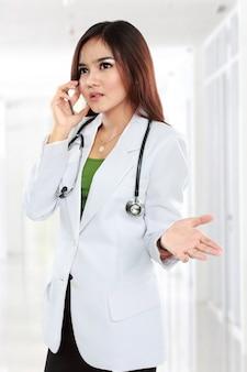 Médica no jaleco com estetoscópio falando pelo celular