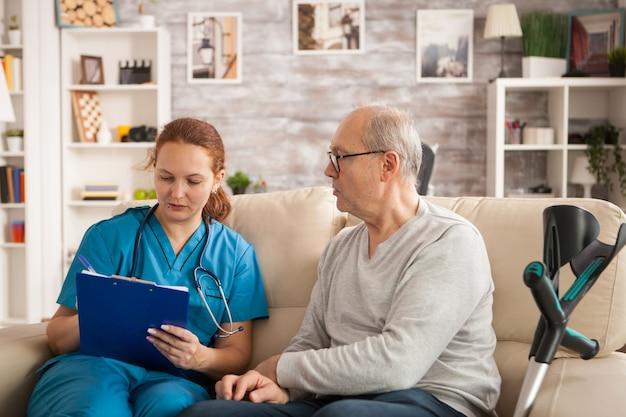 Médica no lar de idosos, tomando notas na área de transferência, enquanto falava com o homem mais velho.