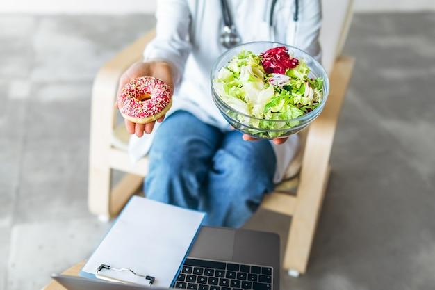 Médica nutricionista segurando comida saudável e junk food nas mãos