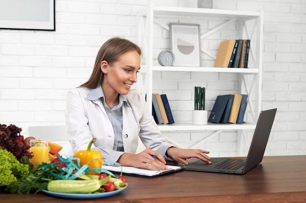 Médica nutricionista sorridente está sentada em seu escritório e trabalha em seu computador