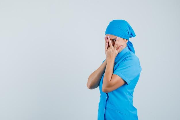 Médica olhando através dos dedos em uniforme azul e curiosa, vista frontal.