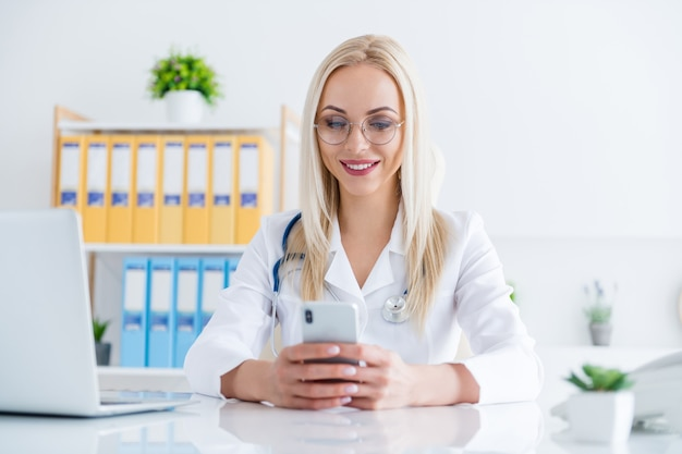 Médica olhando no telefone em seu escritório