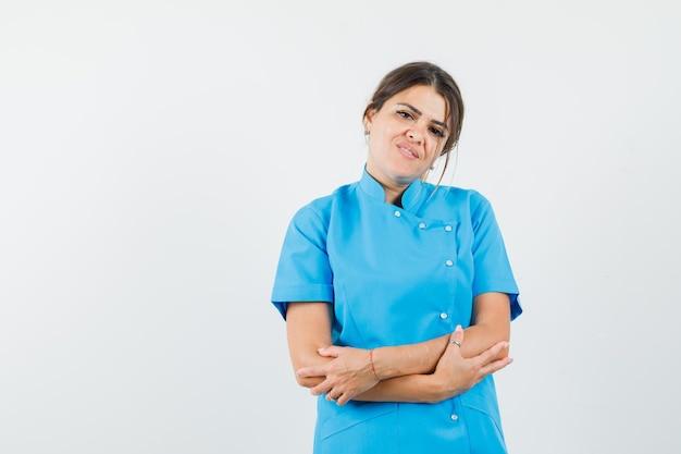 Médica olhando para a câmera de uniforme azul e parecendo esperançosa