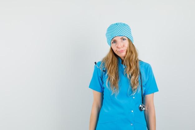Médica olhando para a câmera de uniforme azul e parecendo insatisfeita.