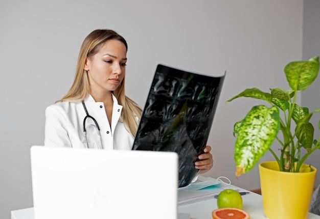 Médica, olhando para a imagem de raio-x