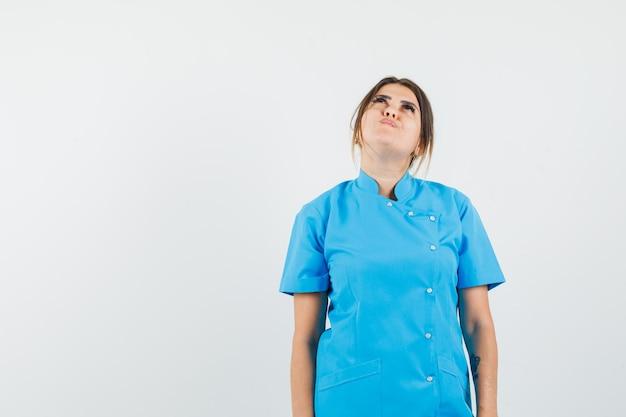 Médica olhando para cima com um uniforme azul e parecendo esperançosa