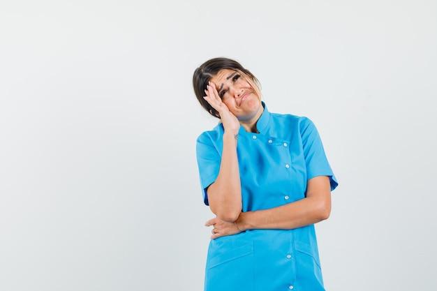 Médica olhando para cima com uniforme azul e parecendo triste