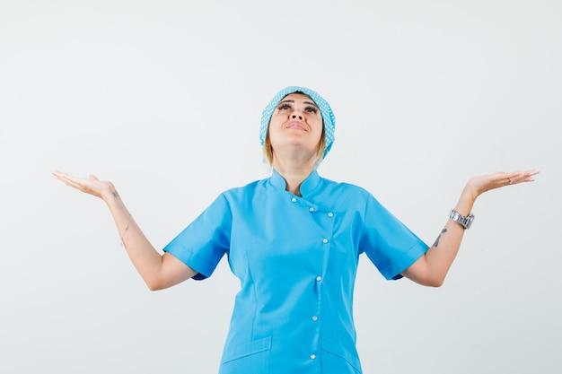 Médica olhando para cima enquanto levanta as mãos com uniforme azul e parecendo esperançosa