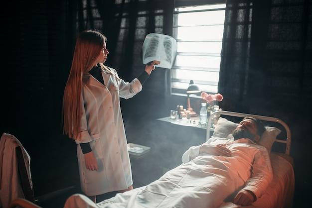 Médica olhando para uma foto de raio-x de um homem doente