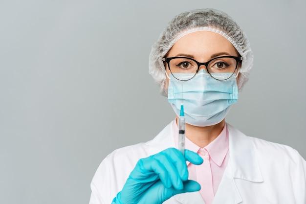 Médica ou cientista com um vestido branco médico, luvas azuis, boné verde e máscara segura uma seringa