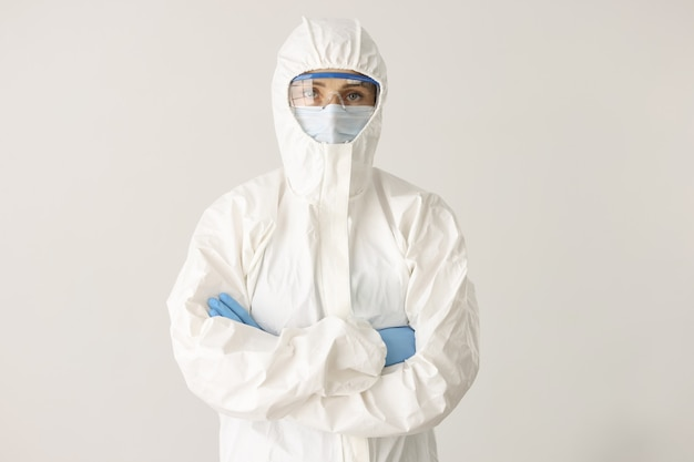 Médica ou cientista usando máscara protetora e óculos com os braços cruzados no branco
