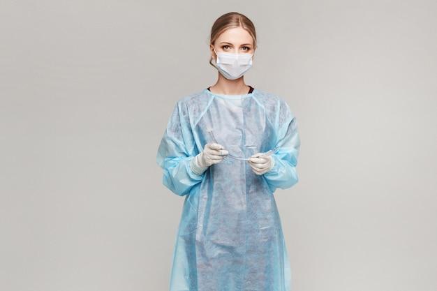 Médica ou cirurgião em uniforme médico e máscara protetora médica segurando o tubo endotraqueal