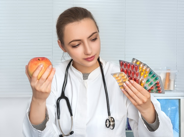 Médica ou dietologista detém maços de comprimidos e uma maçã