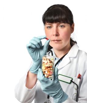 Médica ou enfermeira com copo cheio de comprimidos na mão enluvada.