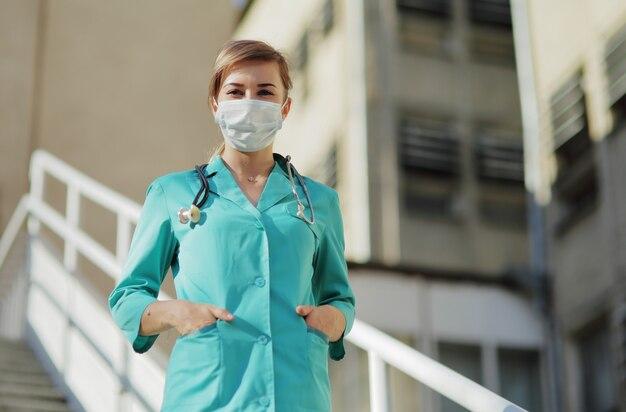Médica ou enfermeira com uma máscara protetora subindo as escadas