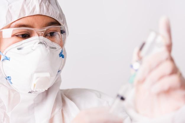 Médica ou enfermeira com uniforme de epi e luvas usando máscara protetora