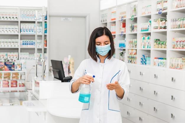 Médica ou farmacêutica turca com máscara médica no rosto usando desinfetante na farmácia
