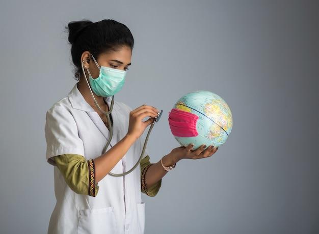 Médica, ouvindo o globo da terra com estetoscópio