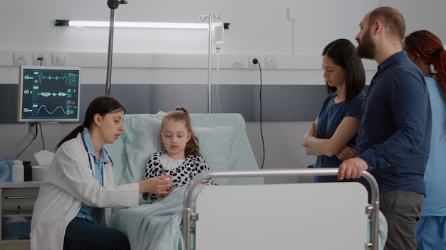 Médica pediatra colocando oxímetro médico no dedo da criança paciente