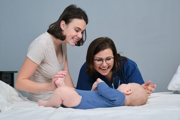 Médica pediatra de uniforme azul com estetoscópio conversando com a jovem mãe de um menino