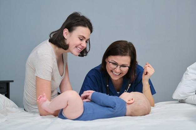 Médica pediatra de uniforme azul com estetoscópio, falando com a jovem mãe de um menino, examinando o bebê de 7 meses em casa. pediatria, cuidado e saúde de crianças até um ano